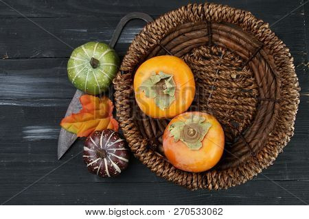 Persimmon On A Wooden Background With Copy Space.