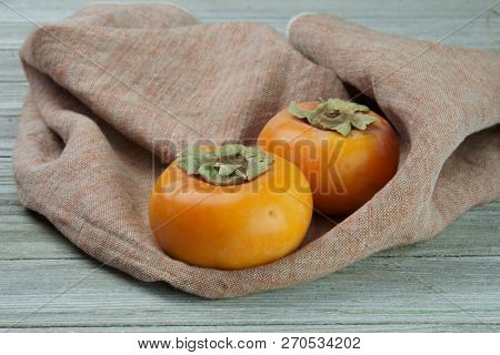 Persimmon On A Wooden Background With A Pommegranate.