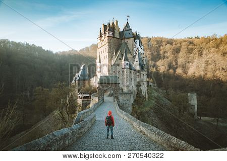 Panorama View Of Young Explorer With Backpack Taking In The View At Famous Eltz Castle At Sunrise In