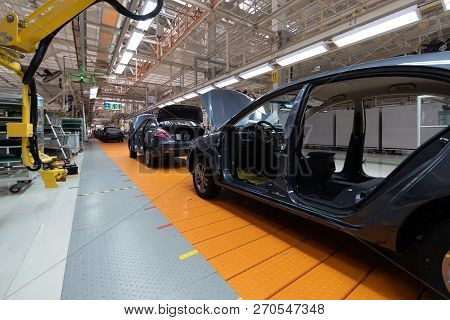 Assembled Car Is On The Assembly Line. Robotic Equipment Makes The Assembly Of The Car. Modern Car A