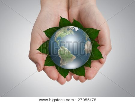 Environmental conservation Concept: Hands  holding earth on leaf
