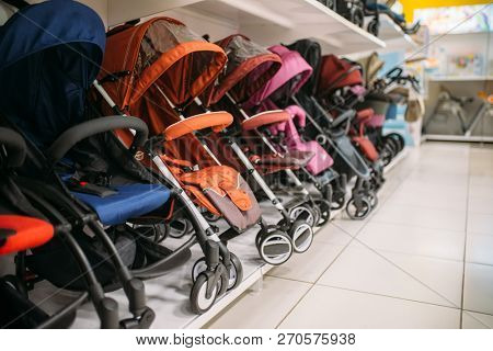 Row of baby strollers on shelf in store, nobody