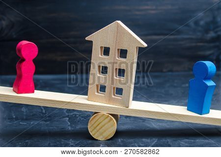 division of property by legal means. clarification of ownership of the house. wooden figures of people. man and woman are standing on the scales. trial, conflict. court. divorce poster