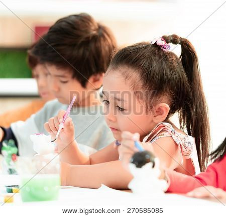Asian Girl And Boys Is Painting On Dolls In Art Group