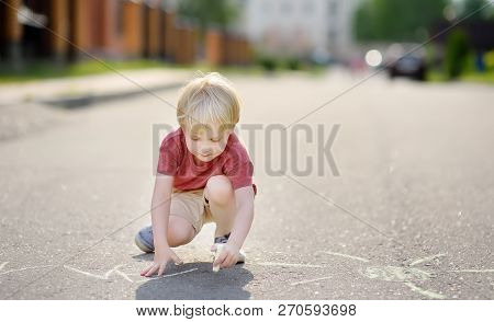 Happy Little Kid Boy Drawing With Colored Chalk On Asphalt. Creative Leisure For Toddler Child In Su