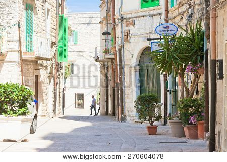 Molfetta, Apulia, Italy - June 3, 2017 - Tourists Entering An Alleyway To A Restaurant