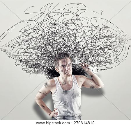 Confused Mechanic In Front Of A White Wall Drawn With Chaotic Lines.the Concept Of Confusion.