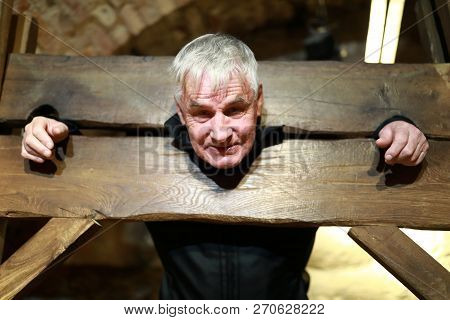 Portrait Of Elderly Man In A Wooden Pillory