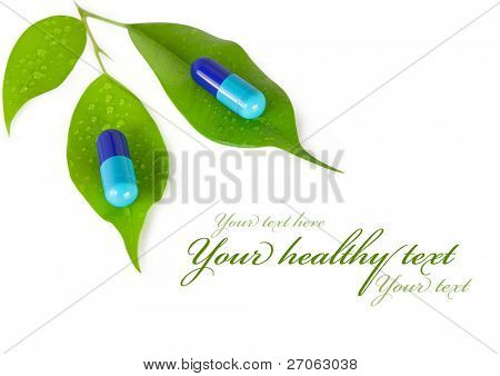 natural medical pills with green leaves. isolated on white background