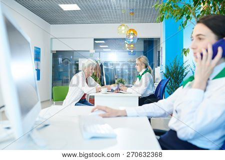 Small Bank Office With Managers At Work: Smiling Blonde Bank Specialist In Green Neck Scarf Sitting