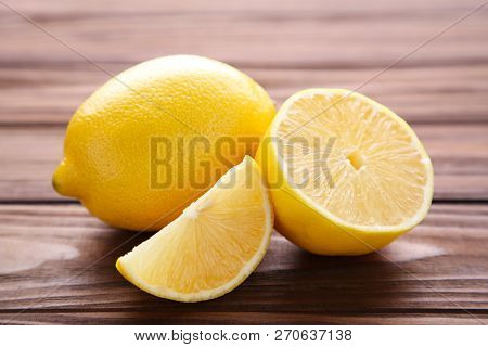 Lemon And Half Of Lemon On Brown Background. Lemon On Brown Wooden Table