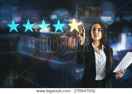 Attractive Young Businesswoman On Blurry City Background With Five Star Rating. Ranking And Feedback
