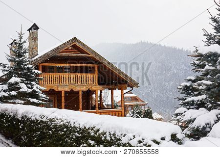 Christmas Wooden Mansion In Mountains On Snowfall Winter Day. Cozy Chalet On Ski Resort Near Pine Fo