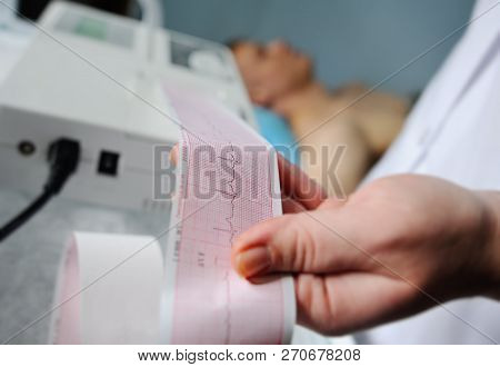 Electrocardiogram, Ecg In Hand. Clinic Cardiology Heart Rhythm And Pulse Test Closeup. Cardiogram Pr