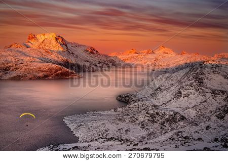 Paraglider flying over the sea during sunset with view on snow covered mountains