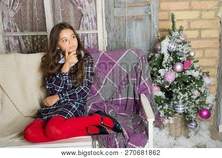 Small Cute Girl Dreaming About Christmas Gift. Kid Dreamy Sit Sofa Dreaming About Christmas Present.