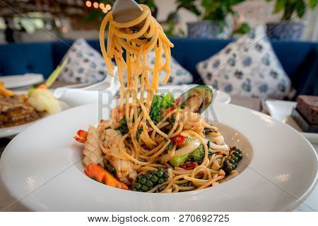 Spicy Seafood Spaghetti Stir Fried (pad Cha) Rolled In The Fork On White Dish Of Luxury Restaurant,