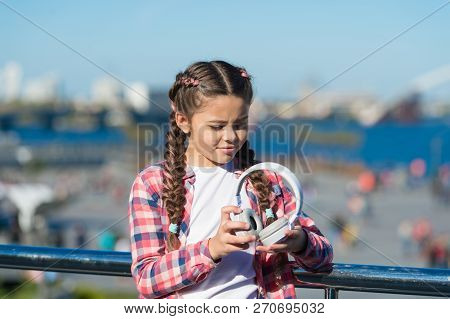 Best Foldable And Portable Headphones. Girl Little Kid Hold Foldable Headphones While Walk Outdoors.