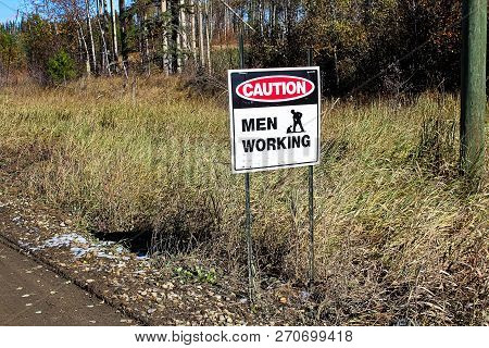 A Caution Men Working Sign Beside A Road