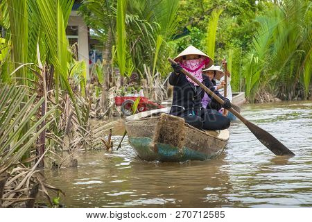 My Tho, Vietnam - November 24, 2018: Vietnamese Women In The Traditional Vietnamese Cap Paddle A Sma