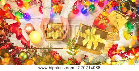 Person putts Christmas gifts boxes on Xmas wooden background. Winter Holiday backdrop. Christmas and New Year decoration, wooden background with Christmas wrapped presents, top view, flatlay.