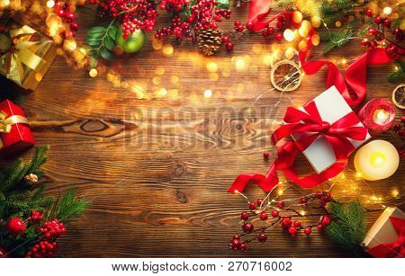 Christmas Gifts background, beautiful Xmas and New Year backdrop with colorful wrapped gifts box, baubles, candles and lighting garland over wooden table background. Top view, flatlay