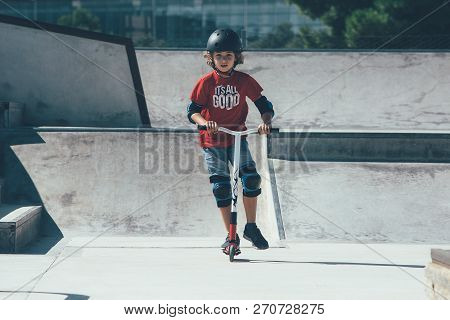 Front View Of A Young Boy Is Wearing A Helmet And The Protections Is Using A Scooter In An Urban Ska