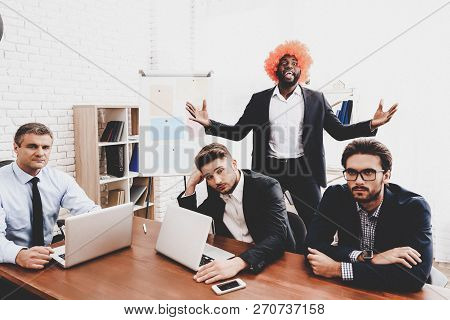 Man In Orange Wig On Business Meeting In Office. April Fools Day. Businessman In Office. April Jokes