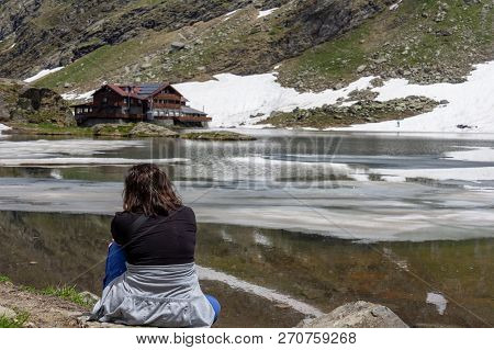 A Woman Hiking Attire Sits Contemplatively On The Lakeshore Looking Toward A Lodge