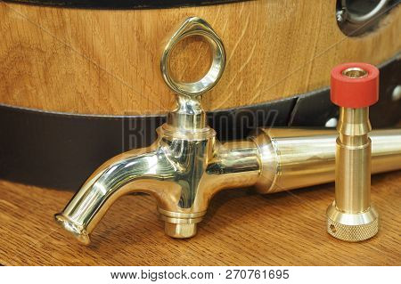 Brass Beer Tap In Front Of A Timber Beer Keg