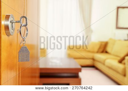 Open Door With Key In Keyhole And Living Room In The Background