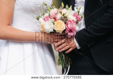 Wedding Bouquet In Couples Hands Outside. Flowers