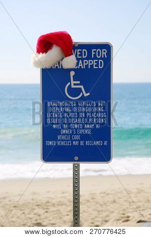 Handicapped parking. Handicapped parking sign with a Santa Hat. Outdoors at the beach with the ocean background. Santa Hat on a Parking Sign outdoors.