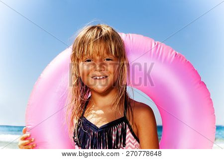 dda9265a39496 Cute Little Girl With Pink Swim Ring On The Beach