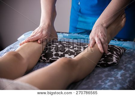Massage Session. Young Woman Lays On The Couch While Getting Anticellulite Massage. Legs Massage