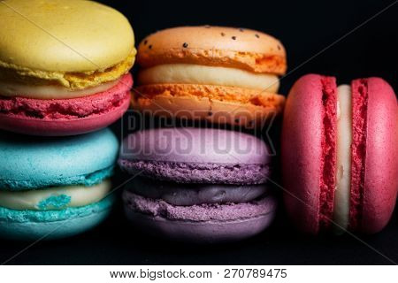Pile of sweet colourful macaroons on black background.
