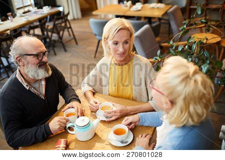 Group of casual friendly senior people having talk by cup of tea in cozy cafe