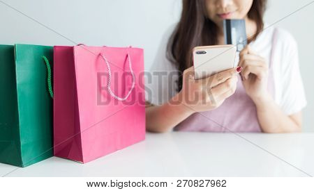 Young Woman Using Smartphone And Holding Credit Card At Home. Online Shopping And Browsing Concept.