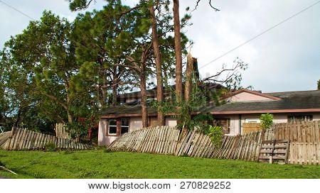 View Of Broken, Blown Over Fence And Broken Tree Tops After Hurricane Irma.  Tree Has Fallen On Hous