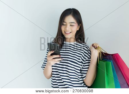 Young Asian Woman Using Smartphone And Holding Shopping Bags. Online Shopping And Browsing Concept.