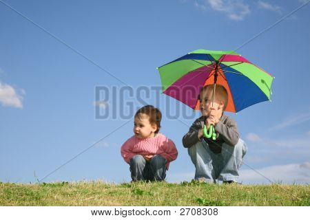 Children On Meadow With Umbrella