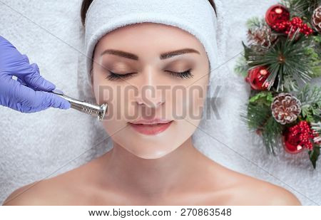 The cosmetologist makes the procedure Microdermabrasion of the facial skin of a beautiful, young woman in a beauty salon.Closeup woman face and new year wreath. poster