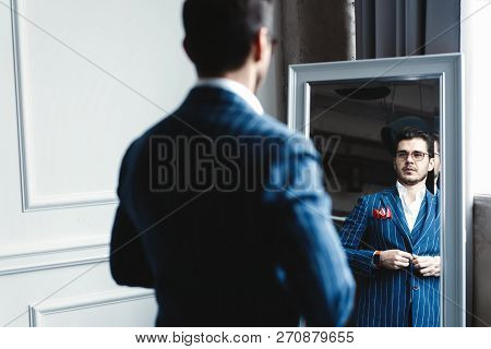 Perfect Look. Reflection Of Handsome Young Man In Full Suit Adjusting His Jacket While Standing In F
