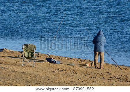 Unrecognizable Fisherman Fishing Alone Dressed In Winter Unrecognizable Fisherman In Winter Parka Wi