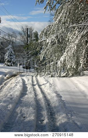A Hazardous, Unplowed, Curving, Snow Covered Road With Tire Tracks Skidding Around Heavy, Snow Laden