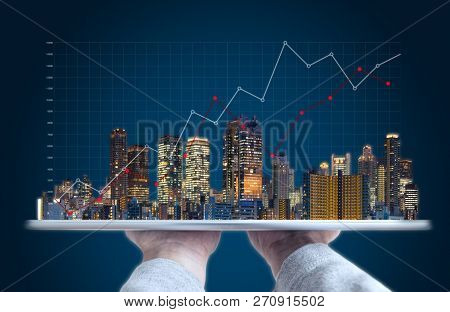 Real Estate Business Investment And Building Technology. Hand Holding Digital Tablet With Buildings