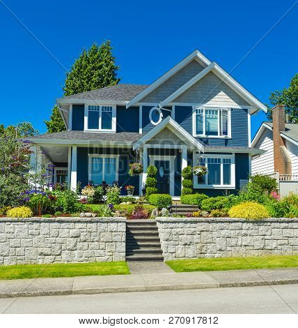 Luxury Family House With Landscaped Front Yard On Land Terrace. Family House On Blue Sky Background