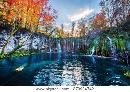 Amazing waterfall with pure blue water in Plitvice lakes. Orange autumn forest on background. Plitvice National Park, Croatia. Landscape photography