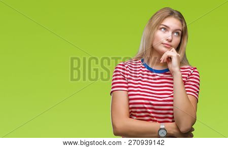 Young caucasian woman over isolated background with hand on chin thinking about question, pensive expression. Smiling with thoughtful face. Doubt concept.