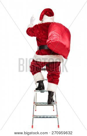 rear view of santa claus with sack on shoulder climbing on a ladder on white background, full length picture